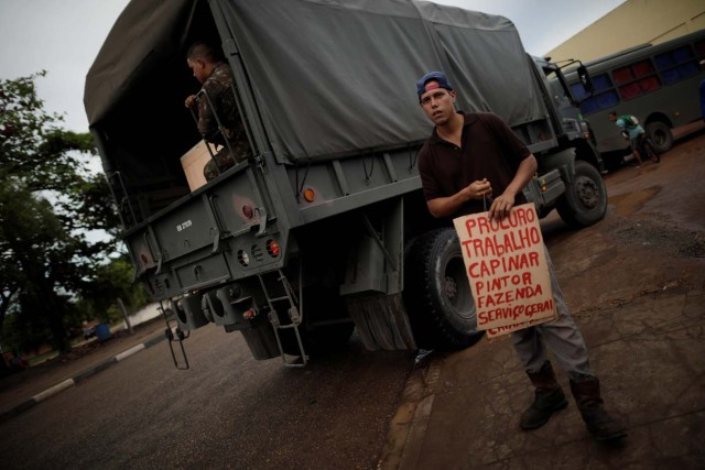 """A Venezuelan migrant carries a placard to apply for a job near a makeshift camp at Simon Bolivar square in Boa Vista, Brazil May 3, 2018. Picture taken May 3, 2018. The placard reads """"Looking for work, carpentry, painting, farming and general services."""" REUTERS/Ueslei Marcelino"""