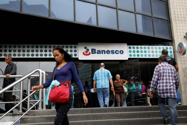 People walk outside a Banesco bank branch in Caracas, Venezuela May 4, 2018. REUTERS/Carlos Garcia Rawlins