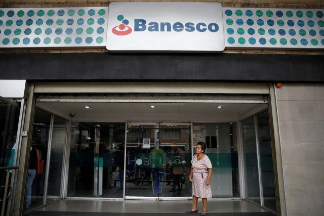 A woman stands at the entrance of a Banesco bank branch in Caracas, Venezuela May 4, 2018. REUTERS/Carlos Garcia Rawlins