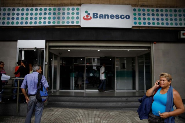 A woman uses her cell phone outside a Banesco bank branch in Caracas, Venezuela May 4, 2018. REUTERS/Carlos Garcia Rawlins