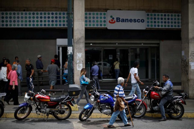 People walk past a Banesco bank branch in Caracas, Venezuela May 4, 2018. REUTERS/Carlos Garcia Rawlins