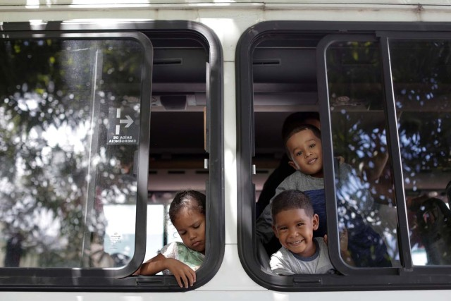 Venezuelan refugee children watch from a bus window as they arrive at UNHCR shelter in Manaus, Brazil May 4, 2018. REUTERS/Bruno Kelly