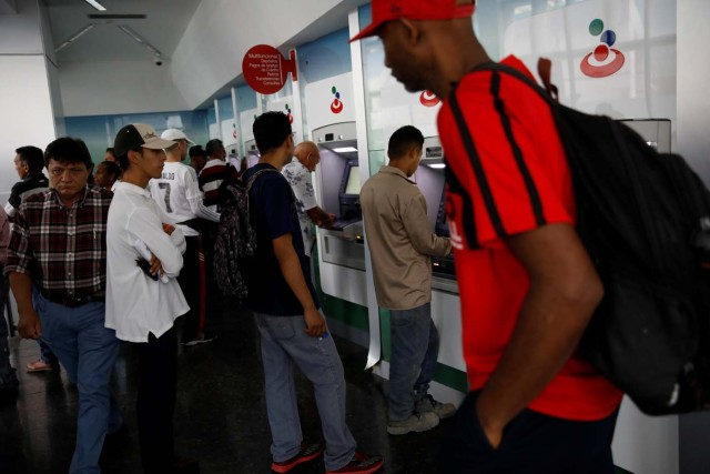 People queue to use the automated teller machines (ATM) at a Banesco bank branch in Caracas, Venezuela May 4, 2018. REUTERS/Carlos Garcia Rawlins