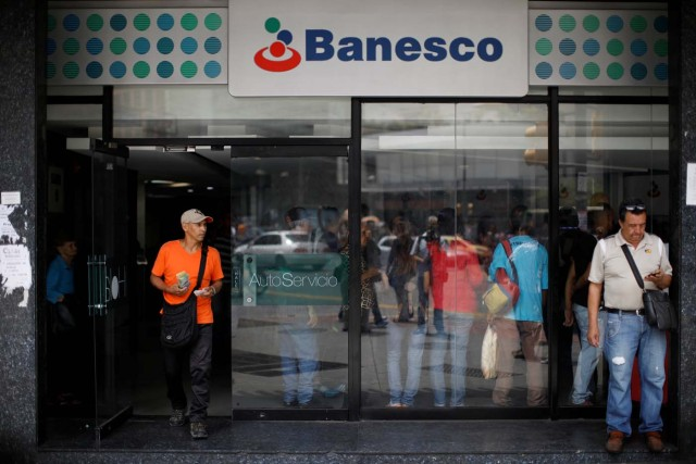 A man walks out from a Banesco bank branch in Caracas, Venezuela May 4, 2018. REUTERS/Carlos Garcia Rawlins