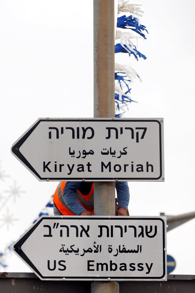 Un trabajador cuelga una señal de tráfico que dirige a la embajada de EE. UU., En el área del consulado de EE. UU. En Jerusalén, el 7 de mayo de 2018. REUTERS / Ronen Zvulun / File Photo