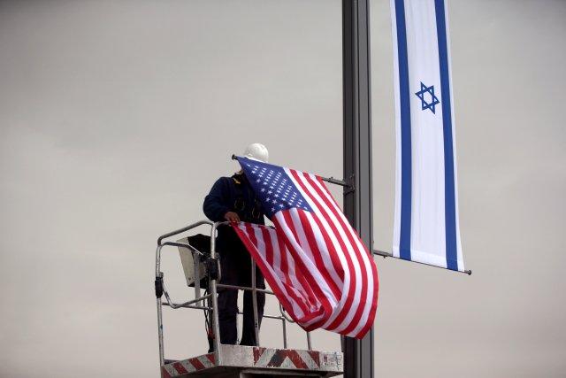 Un trabajador con una grúa cuelga una bandera de EE. UU. Al lado de una bandera israelí, al lado de la entrada al consulado de EE. UU. En Jerusalén, el 7 de mayo de 2018. REUTERS / Ronen Zvulun / Archivo de foto