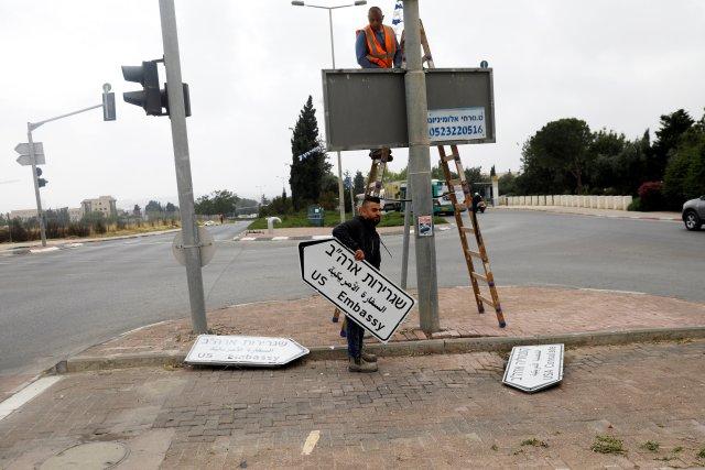 Un trabajador sostiene un letrero que dirige a la embajada de los EE. UU., En el área del consulado de EE. UU. En Jerusalén, el 7 de mayo de 2018. REUTERS / Ronen Zvulun / File Photo