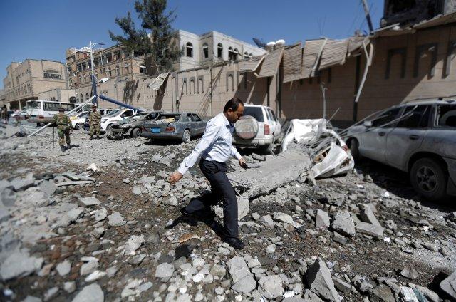 Un hombre pasa frente a automóviles dañados fuera del complejo presidencial después de que fue alcanzado por ataques aéreos en Sanaa, Yemen, el 7 de mayo de 2018. REUTERS / Khaled Abdullah