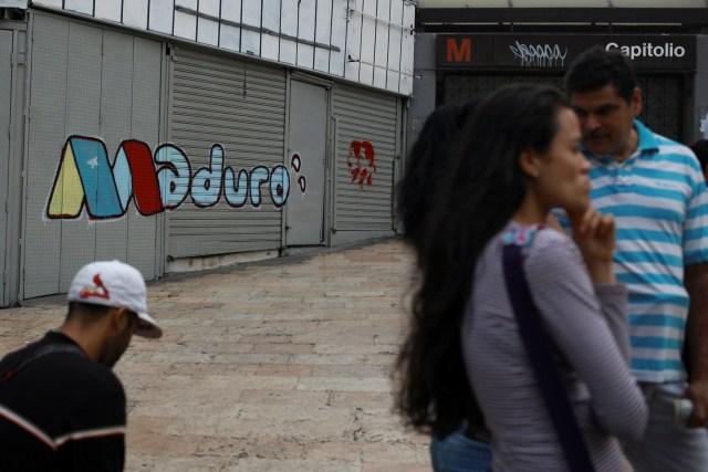 La gente se para frente a un graffiti de campaña del presidente venezolano, Nicolás Maduro, en Caracas, Venezuela, el 6 de mayo de 2018. Fotografía tomada el 6 de mayo de 2018. REUTERS / Adriana Loureiro