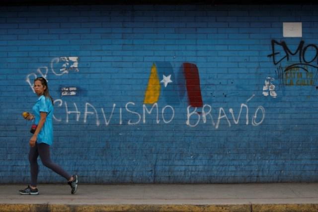 Una mujer pasa frente a un graffiti de campaña a favor del presidente de Venezuela, Nicolás Maduro, en Caracas. Mayo 8, 2018. REUTERS/Adriana Loureiro