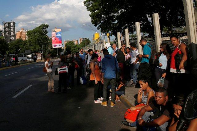 Los carteles de campaña del presidente venezolano, Nicolás Maduro, para las elecciones presidenciales de 2018 se ven en la calle mientras la gente espera un autobús en Caracas, Venezuela, el 11 de mayo de 2018. Fotografía tomada el 11 de mayo de 2018 REUTERS / Carlos Jasso