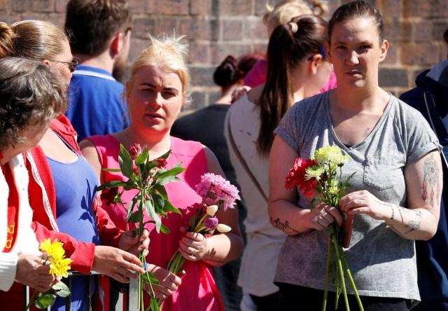 Las personas que llevan tributos florales esperan que el cortejo fúnebre del niño Alfie Evans pase Goodison Park, el estadio del club de fútbol Everton, en Liverpool, Reino Unido, el 14 de mayo de 2018. REUTERS / Phil Noble