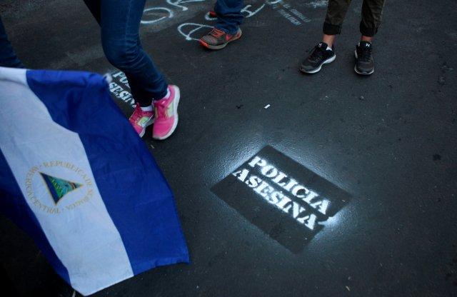 """Los manifestantes caminan junto a un graffiti que dice """"Policía asesina"""" durante una protesta contra el gobierno del presidente de Nicaragua, Daniel Ortega, en Managua, Nicaragua, el 15 de mayo de 2018. REUTERS / Oswaldo Rivas"""