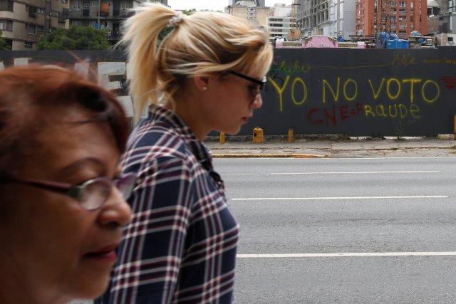"""Las mujeres caminan más allá de los graffiti pintados en una valla en Caracas, Venezuela, 13 de mayo de 2018. Graffiti dice: """"No voy a votar"""". Fotografía tomada el 13 de mayo de 2018. REUTERS / Carlos Jasso"""