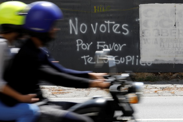"""Una motocicleta atraviesa delante de un graffiti pintado en una barda en Caracas, Venezuela, 12 de mayo, 2018. El grafiti dice: """"No votes, por favor te lo suplico"""". REUTERS/Carlos Jasso - RC1B4B72EEA0"""