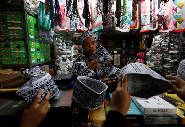 A man sells prayer caps on the eve of the Muslim fasting month of Ramadan at a traditional market in Jakarta, Indonesia, May 16, 2018. REUTERS/Willy Kurniawan