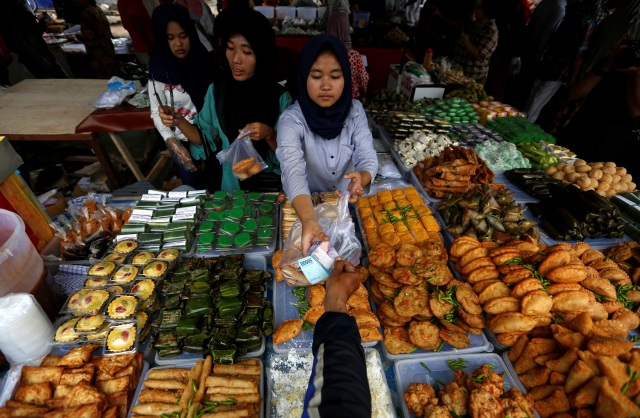 A vendor sells food for iftar on the first day of the holy fasting month of Ramadan at a traditional food market in Jakarta, Indonesia, May 17, 2018. REUTERS/Willy Kurniawan