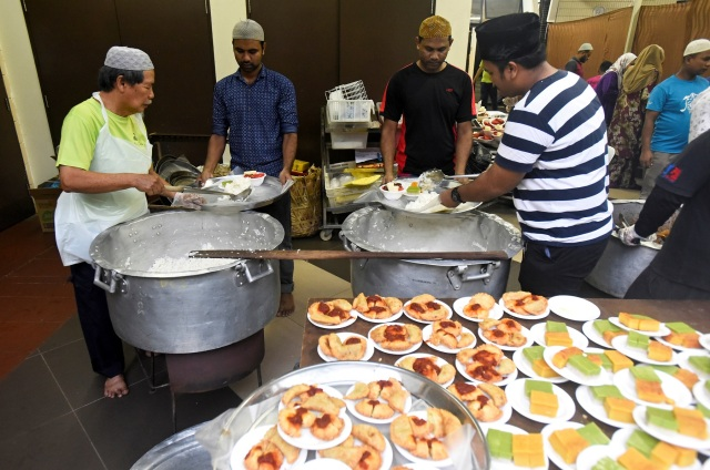 Volunteers prepare food for iftar on the first day of the holy fasting month of Ramadan at the Darul Makmur Mosque in Singapore, May 17, 2018. REUTERS/Feline Lim