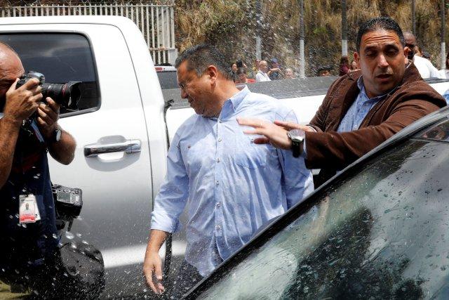 """El candidato presidencial venezolano Javier Bertucci, del partido """"Esperanza por el Cambio"""", reacciona después de que un pariente arroja agua afuera de un centro de detención del Servicio Bolivariano de Inteligencia Nacional (SEBIN) en Caracas, Venezuela el 17 de mayo de 2018. REUTERS / Carlos Jasso"""