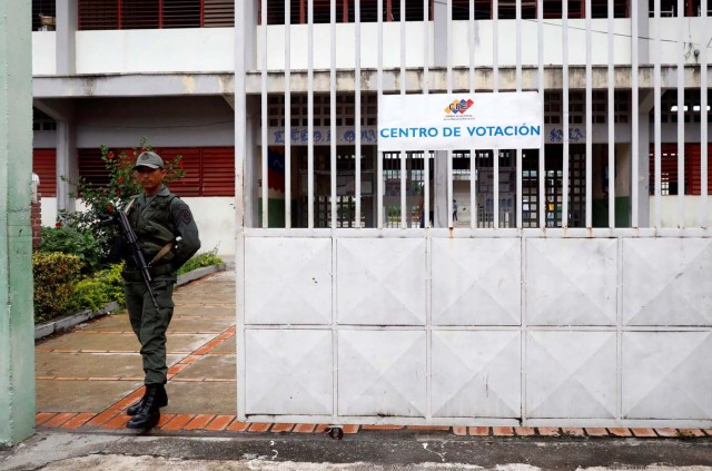 A member of the security forces mount guard at the door of a polling station during the presidential election in Barquisimeto, Venezuela, May 20, 2018. REUTERS/Carlos Jasso