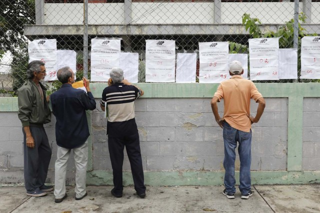 Venezuelan citizens check electoral lists at a polling station during the presidential election in Barquisimeto, Venezuela, May 20, 2018. REUTERS/Carlos Jasso