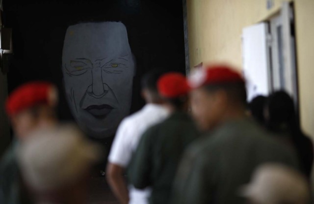With an image of the late Venezuelan President Hugo Chavez on a wall Venezuelan soldiers and cititzens wait to cast their votes at a polling station during the presidential election in Caracas, Venezuela, May 20, 2018. REUTERS/Carlos Garcia Rawlins
