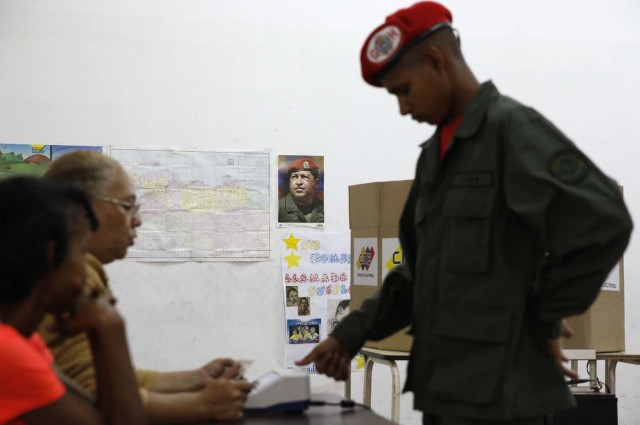With an image of the late Venezuelan President Hugo Chavez on the wall a Venezuelan soldier marks his thumb print as he prepares to cast his vote at a polling station during the presidential election in Caracas, Venezuela, May 20, 2018. REUTERS/Carlos Garcia Rawlins