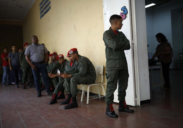 Venezuelan soldiers and civilians wait to cast their votes at a polling station during the presidential election in Caracas, Venezuela, May 20, 2018. REUTERS/Carlos Garcia Rawlins
