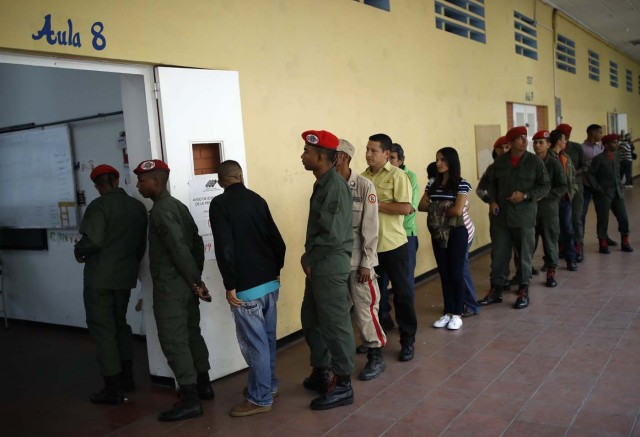 REFILE - CORRECTING TYPO - Venezuelan soldiers and citizens wait to cast their votes at a polling station during the presidential election in Caracas, Venezuela, May 20, 2018. REUTERS/Carlos Garcia Rawlins