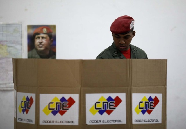 With an image of the late Venezuelan President Hugo Chavez behind him a Venezuelan soldier casts his vote at a polling station during the presidential election in Caracas, Venezuela, May 20, 2018. REUTERS/Carlos Garcia Rawlins