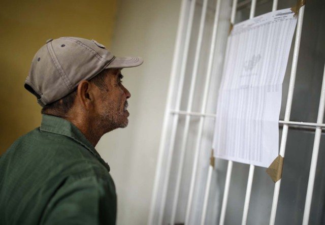 A Venezuelan voter checks an electoral list at a polling station during the presidential election in Caracas, Venezuela, May 20, 2018. REUTERS/Carlos Garcia Rawlins