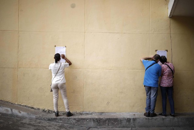 Venezuelan citizens check electoral lists at a polling station during the presidential election in Caracas, Venezuela, May 20, 2018. REUTERS/Carlos Garcia Rawlins