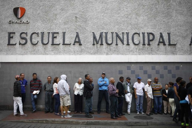 Venezuelan citizens wait in line to vote at a polling station situated inside a school during the presidential election in Caracas, Venezuela, May 20, 2018. REUTERS/Adriana Loureiro