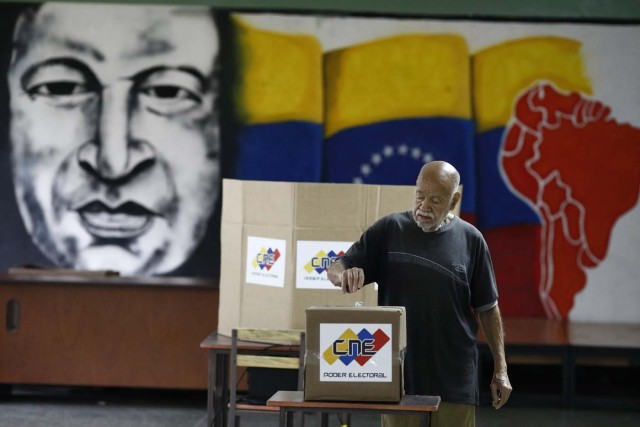 With an image of the late Venezuelan President Hugo Chavez behind him a Venezuelan citizen casts his vote at a polling station during the presidential election in Caracas, Venezuela, May 20, 2018. REUTERS/Marco Bello