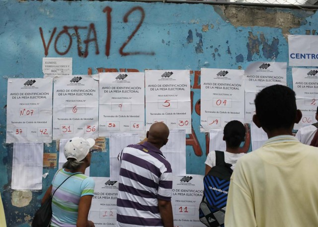 Venezuelan citizens check electoral lists at a polling station during the presidential election in Caracas, Venezuela, May 20, 2018. REUTERS/Adriana Loureiro