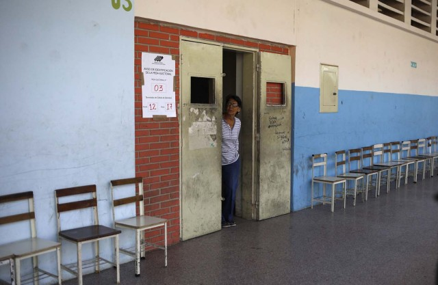A woman peers out of a door as a polling station stands empty during the presidential election in Caracas, Venezuela, May 20, 2018. REUTERS/Adriana Loureiro