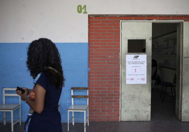 A woman walks past a nearly empty polling station during the presidential election in Caracas, Venezuela, May 20, 2018. REUTERS/Adriana Loureiro