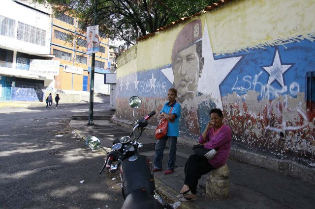 Women wait by a mural of the late Venezuelan President Hugo Chavez during the presidential election in Caracas, Venezuela, May 20, 2018. REUTERS/Adriana Loureiro Fernandez