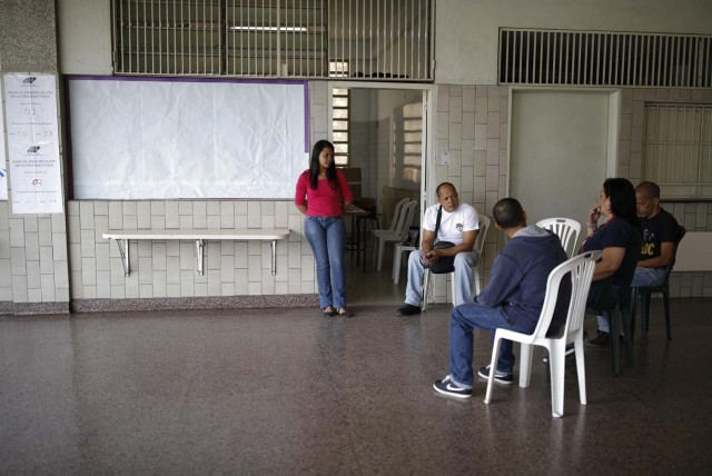 Electoral officials await voters at a polling station during the presidential election in Caracas, Venezuela, May 20, 2018. REUTERS/Carlos Garcia Rawlins