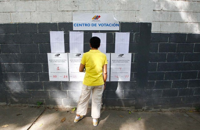 A woman checks electoral lists at a polling station during the presidential election in Caracas, Venezuela, May 20, 2018. REUTERS/Christian Veron