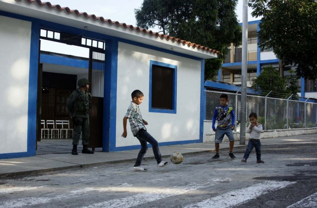 Youths kick a ball in front of a polling station during the presidential election in San Cristobal, Venezuela, May 20, 2018. REUTERS/Carlos Eduardo Ramirez