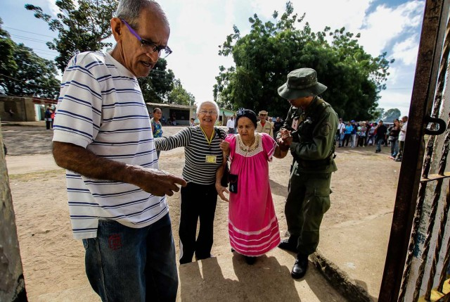 A Venezuelan is assisted while waiting with others to vote at a polling station during the presidential election in Puerto Ordaz, Venezuela, May 20, 2018. REUTERS/William R. Urdaneta