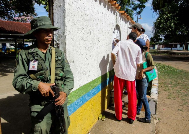 A soldier stands guard as people check electoral lists at a polling station during the presidential election in Puerto Ordaz, Venezuela, May 20, 2018. REUTERS/William R. Urdaneta