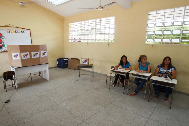 Electoral workers wait for voters at a polling station during the presidential election in Maracaibo, Venezuela, May 20, 2018. REUTERS/Isaac Urrutia Jose Bula