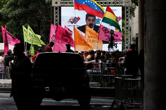 Los simpatizantes miran al presidente electo de Venezuela, Nicolás Maduro, en una pantalla después de recibir un certificado que lo confirma como ganador de las elecciones del domingo, frente al Consejo Nacional Electoral (CNE) en Caracas, Venezuela el 22 de mayo de 2018. REUTERS / Carlos Garcia Rawlins