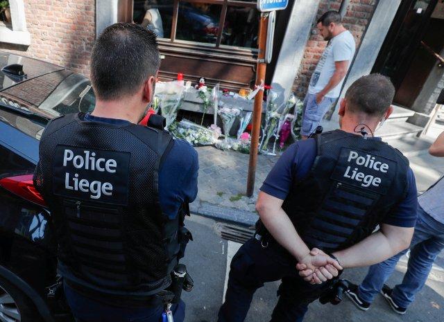 Los policías belgas rinden homenaje a las víctimas de un tiroteo en el exterior del café donde se produjo el tiroteo en Lieja, Bélgica, el 30 de mayo de 2018. REUTERS / Yves Herman