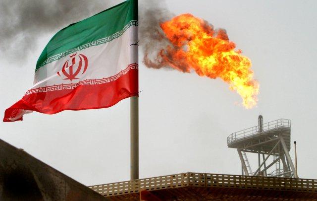 Imagen de archivo de una bandera de Irán junto a una llama en una plataforma de producción en los yacimientos de crudo de Soroush, en el Golfo Pérsico. 25 julio 2005. REUTERS/Raheb Homavandi