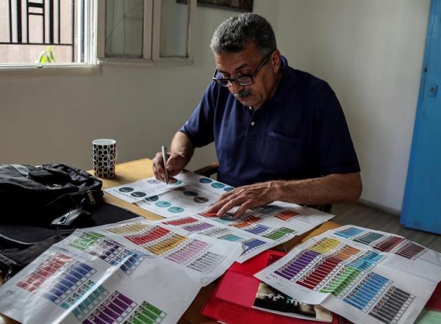 (LÍBANO), 03/05/2018.- Un ciudadano libanés inspecciona listas de candidatos hoy, jueves 3 de mayo de 2018, durante las campañas para las elecciones parlamentarias libanesas, en Beirut (Líbano). Un total de 976 candidatos, incluidas 111 mujeres, presentaron sus documentos de candidatura al Ministerio del Interior, lo que representa la mayor cantidad de candidatos jamás registrados. Las elecciones generales del 06 de mayo de 2018 serán las primeras del Líbano en nueve años. EFE/Nabil Mounzer