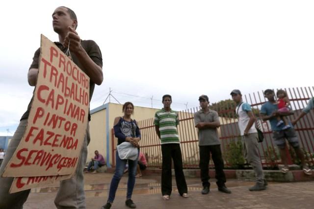 """BRA105. BOA VISTA (BRASIL), 03/05/2018 - Un refugiados venezolano con una pancarta pidie empleo hoy, jueves 3 de mayo de 2018, frente al refugio mantenido por el alto comisionado de las Naciones Unidas para los refugiados, en la ciudad de Boa Vista, capital del estado de Roraima (Brasil). Unos 6.000 venezolanos están en una situación de """"vulnerabilidad"""" en Boa Vista, punto de llegada para muchos de los que huyen de la crisis en ese país caribeño, informaron hoy fuentes oficiales. EFE/Joédson Alves"""