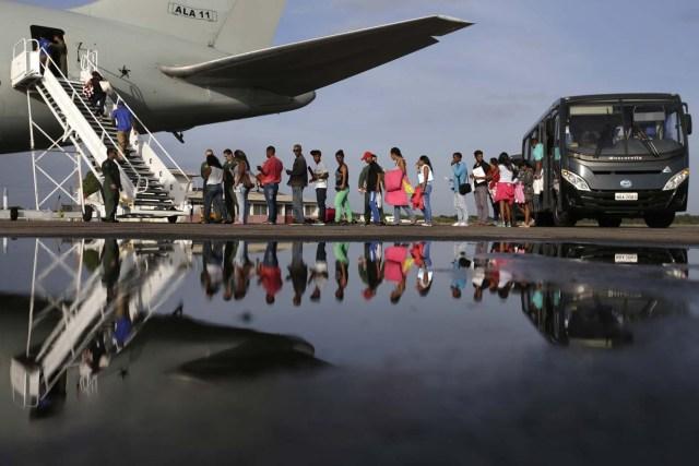 BSL03. BOA VISTA (BRASIL), 04/05/2018.- Venezolanos ingresan a un avión en el aeropuerto de Boa Vista (Brasil) hoy, viernes 4 de mayo de 2018. Las autoridades brasileñas trasladaron desde Boa Vista, el principal punto de acogida de la inmigración venezolana, a 233 ciudadanos de esa nación caribeña que han decidido intentar rehacer sus vidas en Sao Paulo y Manaus. Todos partieron en el mismo avión de la Fuerza Aérea Brasileña y 164 desembarcarían en la primera escala, en la amazónica Manaus, en tanto que los otros 69 seguirían viaje hasta Sao Paulo, la ciudad más poblada del país, donde esperan dejar definitivamente atrás la crisis económica, social y política en que se ha hundido Venezuela. EFE/Joédson Alves